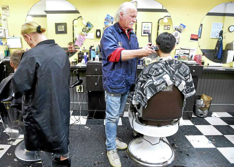 Carl McManus, center, cuts the hair of Yale junior Kevin Hwang at Phil's Hair Styles on Wall Street in New Haven on 11/24/2015. McManus has been at Phil's Hair Styles for 50 years. Photo: Arnold Gold — New Haven Register