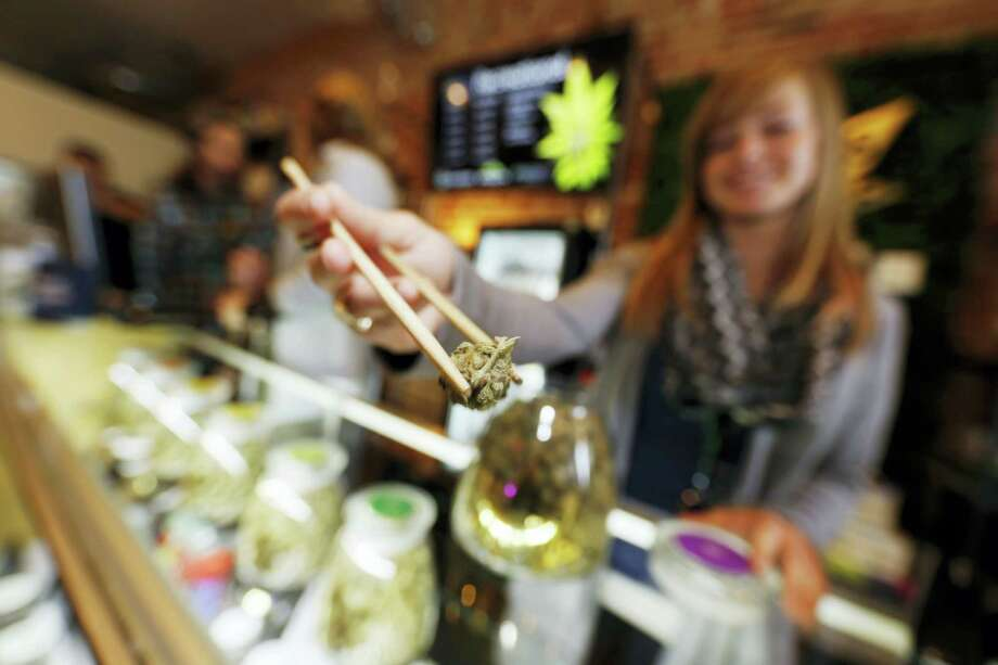 In this Dec. 18 photos, LivWell store manager Carlyssa Scanlon shows off some of the products available in the marijuana line marketed by rapper Snoop Dogg in one of the marijuana chain's outlets south of downtown Denver. LivWell grows the Snoop pot alongside many other strains on its menu. Photo: Associated Press/David Zalubowski   / AP