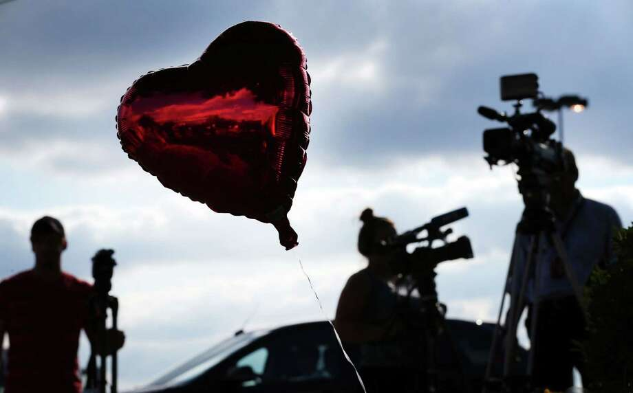 Reporters gather around a memorial of balloons and flowers placed outside of  WDBJ7's Digital Broadcast Center in Roanoke, Va., Wednesday, Aug. 26, 2015. The shooting of a television reporter and a cameraman unfolded on live TV before an audience of tens of thousands on the smaller market central Virginia television station. Photo: Heather Rousseau/The Roanoke Times Via AP    / HEATHER ROUSSEAU | The Roanoke Times