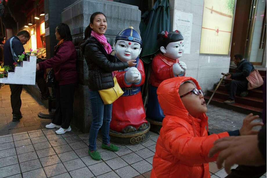 AP Photo/Ng Han Guan  A woman gestures towards two dolls depicting children near a child in Beijing, China on Oct. 29, 2015. The official Xinhua News Agency says China's ruling Communist Party has decided to abolish the country's one-child policy and allow all couples to have two children. Photo: AP / AP