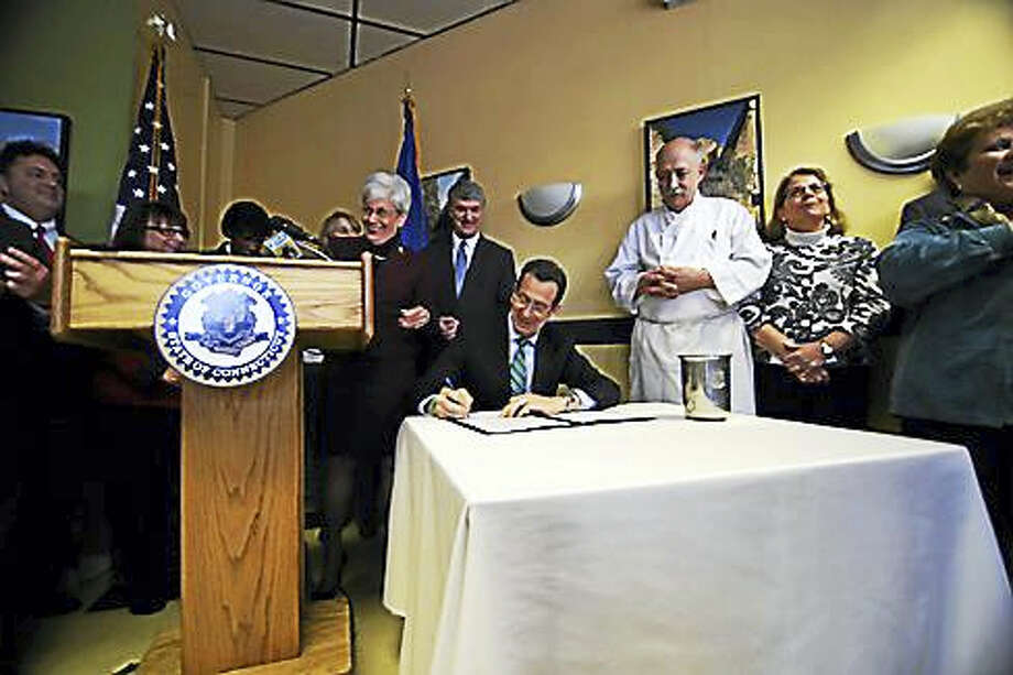 Gov. Dannel P. Malloy signs the minimum wage law in 2014. Photo: Christine Stuart — CT News Junkie File Photo