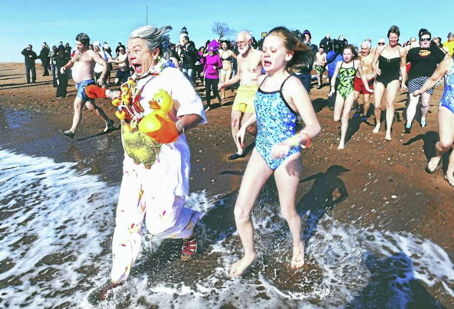 Liz Duckrow, left center, of New Haven leads the charge into the Long Island Sound for the Polar Plunge for Parks at Lighthouse Point Park in New Haven last year. Photo: Arnold Gold-New Haven Register File