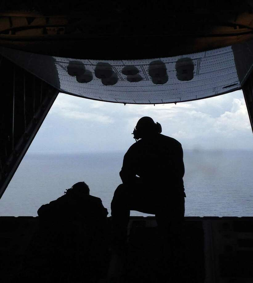 Petty Officer 3rd Class Charles Camarda, left, and Petty Officer 3rd Class Nate Matthews scour the Atlantic Ocean off the coast of Savannah, Ga., Tuesday, looking for two missing teenage boaters. Camarda and Matthews are crew members from Air Station Clearwater, Florida. Photo: AP Photo/Tamara Lush / AP