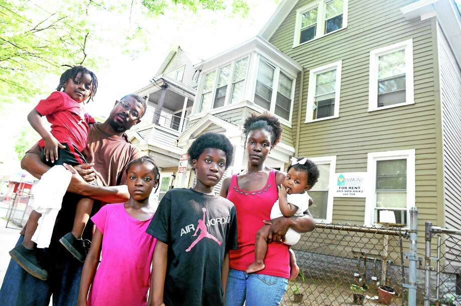 Left to right, Caleb Fernandez, 3, his father, Prudencio, sister, Trinity, 8, brother, Jamario, 10, mother, Ceria, and sister, Asani, 8 months, are photographed in front of their second floor apartment at 375 Shelton Ave. in New Haven that is undergoing repair from water damage and mold on 8/18/2015. Photo: (Arnold Gold — New Haven Register)