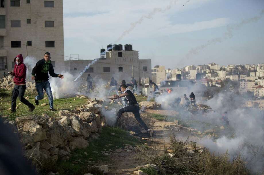 Palestinian protesters run from tear gas fired by Israeli troops during clashes outside Ofer military prison near the West Bank city of Ramallah, Friday, Nov. 27, 2015. Photo: AP Photo/Majdi Mohammed / AP