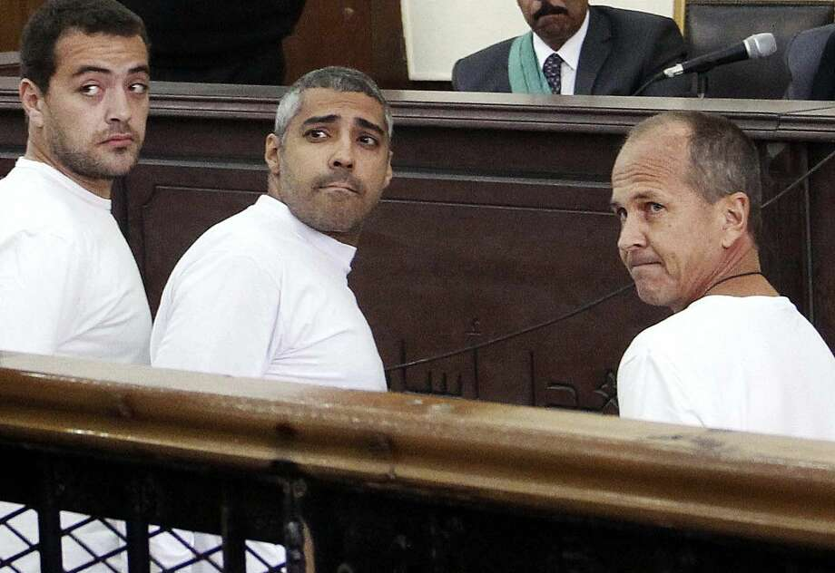 FILE - In this March 31, 2014 file photo, Al-Jazeera English producer Baher Mohamed, left, Canadian-Egyptian acting Cairo bureau chief Mohammed Fahmy, center, and correspondent Peter Greste, right, appear in court along with several other defendants during their trial on terror charges, in Cairo. An Egyptian court on Saturday, Aug. 29, 2015, sentenced the three Al-Jazeera English journalists to three years in prison. Photo: (AP Photo/Heba Elkholy, El Shorouk, File)  / EL Shorouk