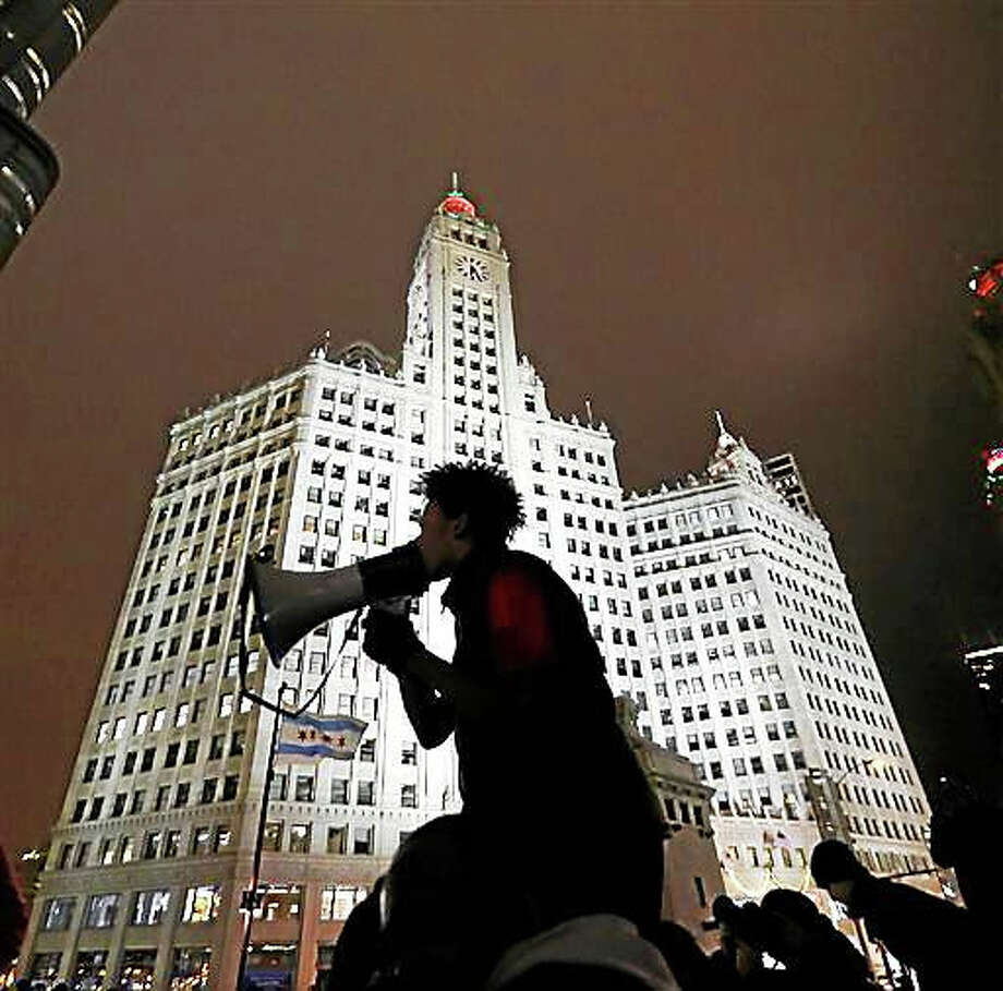 A protester is silhouetted against Chicago's famed Wrigley Building as he directs others to shutdown traffic on both sides of the Michigan Ave. bridge over the Chicago River, Wednesday, Nov. 25, 2015, one day after murder charges were brought against police officer Jason Van Dyke in the killing of 17-year-old Laquan McDonald. Photo: AP Photo/Charles Rex Arbogast    / AP