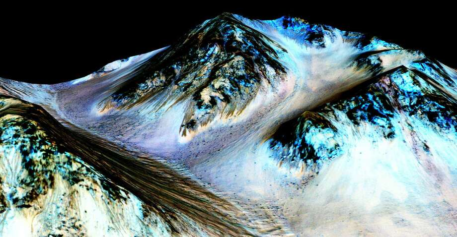 This undated photo provided by NASA and taken by an instrument aboard the agency's Mars Reconnaissance Orbiter shows dark, narrow, 100 meter-long streaks on the surface of Mars that scientists believe were caused by flowing streams of salty water. Researchers said Monday, Sept. 28, 2015, that the latest observations strongly support the longtime theory that salt water in liquid form flows down certain Martian slopes each summer. (NASA/JPL/University of Arizona via AP) Photo: AP / NASA