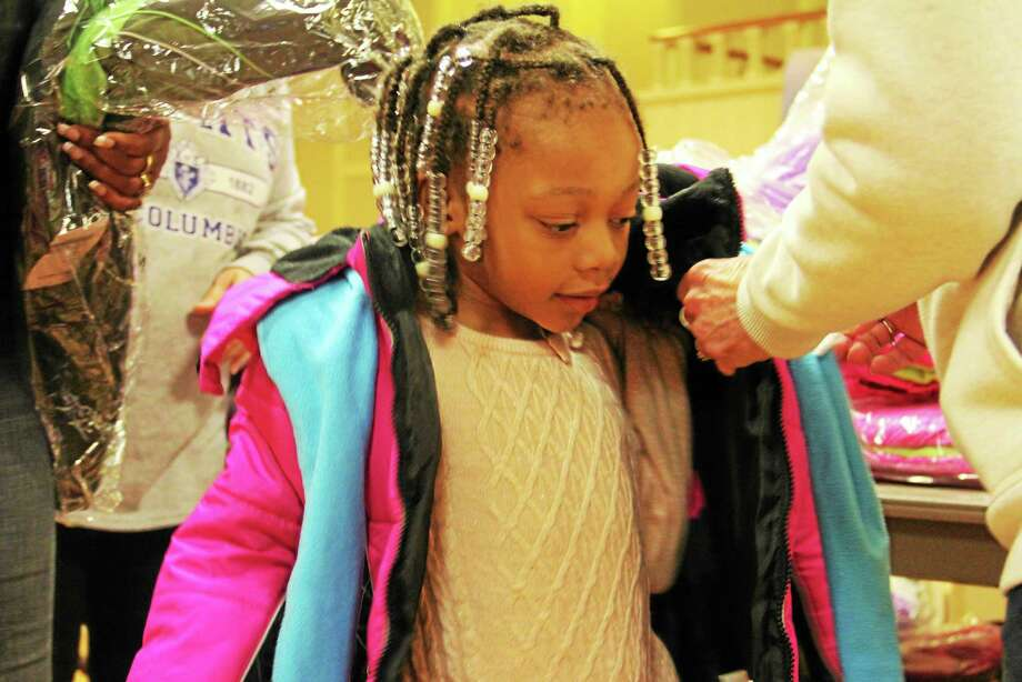 Volunteers at the Knights of Columbus coat drive help Liah Mills, 3, try on a jacket Friday at St. Mary's Church in New Haven. Photo: Esteban L. Hernandez — New Haven Register