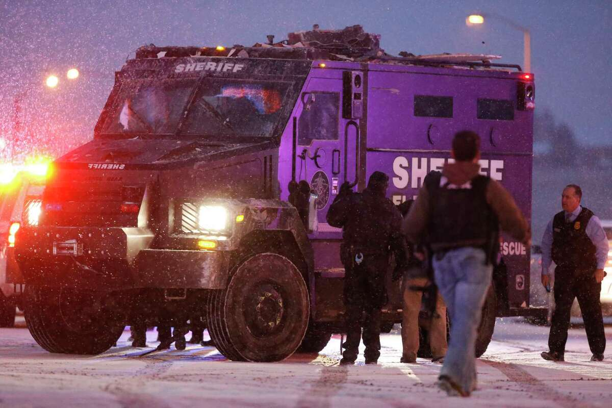 A police vehicle carries a suspect away from the intersection of Centennial and Fillmore after a shooting at a Planned Parenthood clinic Friday, Nov. 27, 2015, in Colorado Springs, Colo.