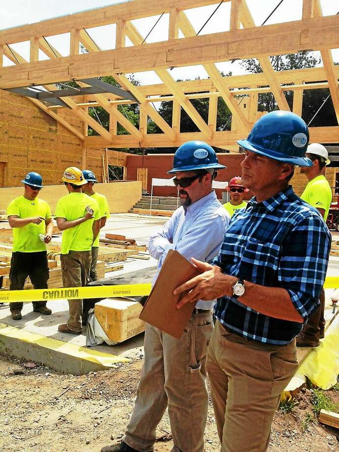 Chris Carbone, foreground, structural engineer for Bensonwood, and Jean-Marc Dubois, director of business development for Nordic, explain sustainable elements in the addition at Common Ground High School Wednesday in New Haven. Photo: Mary O'Leary — New Haven Register
