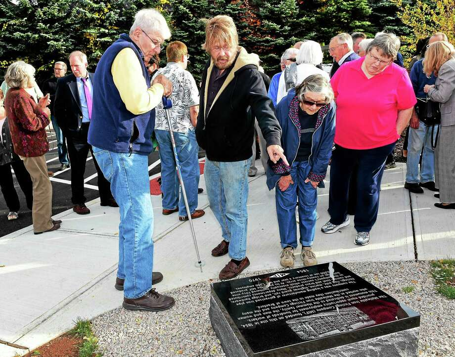From left, Joe Ifkovic of Branford, his cousin David Ifkovic of Easton, far right, Betty Ann Trapasso of Branford and Marilyn Lehr of Branford take a closer look at a newly installed commemorative granite stone in front of the Stony Creek Brewery in Branford, the former site of Malleable Iron Fittings, before a formal dedication of the monument Thursday afternoon in Branford. Photo: Peter Hvizdak — New Haven Register   / ©2015 Peter Hvizdak