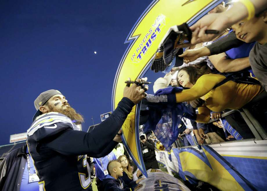 Chargers free safety Eric Weddle signs autographs after their win against the Dolphins earlier this year. Photo: The Associated Press   / AP