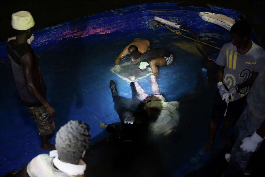 In this Thursday, Aug. 27, 2015, photo, bodies of migrants are pulled from a hole in the deck after their boat sank off the coast of in Zuwara, Libya. It was not clear how many migrants drowned. Dozens of boats are launched from lawless Libya each week, with Italy and Greece bearing the brunt of the surge. Photo: AP Photo/Mohamed Ben Khalifa    / AP