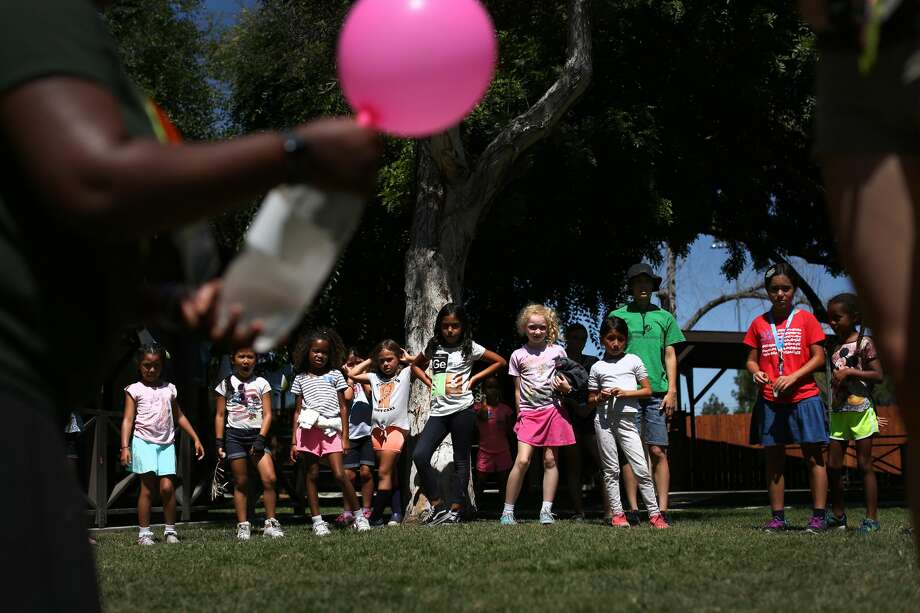 Girl Scouts watch an experiment during a summer day camp in Long Beach, on July 3, 2017. Girl Scout troops of girls ages 5 to 17 are being taught everything from robotics to video game design these days, and now the organization is adding cybersecurity to its list of badges and patches. (Rick Loomis/Los Angeles Times/TNS) Photo: Rick Loomis/TNS
