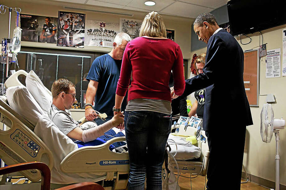 President Barack Obama prays with a wounded service member and his family during a visit to Walter Reed National Military Medical Center in Bethesda, Maryland, in June 2012. Photo: Photo-Pete Souza/White House. / The White House