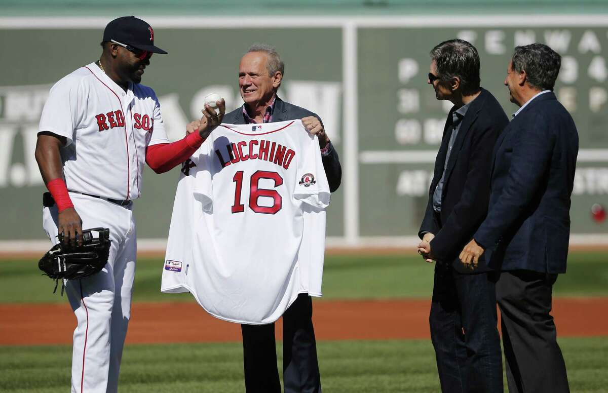 David Ortiz, left, presents Red Sox president and CEO Larry Lucchino, second from left, with a jersey and a ball as team owner John Henry, second from right, and chairman Tom Werner watch during a tribute before the Sunday's game.