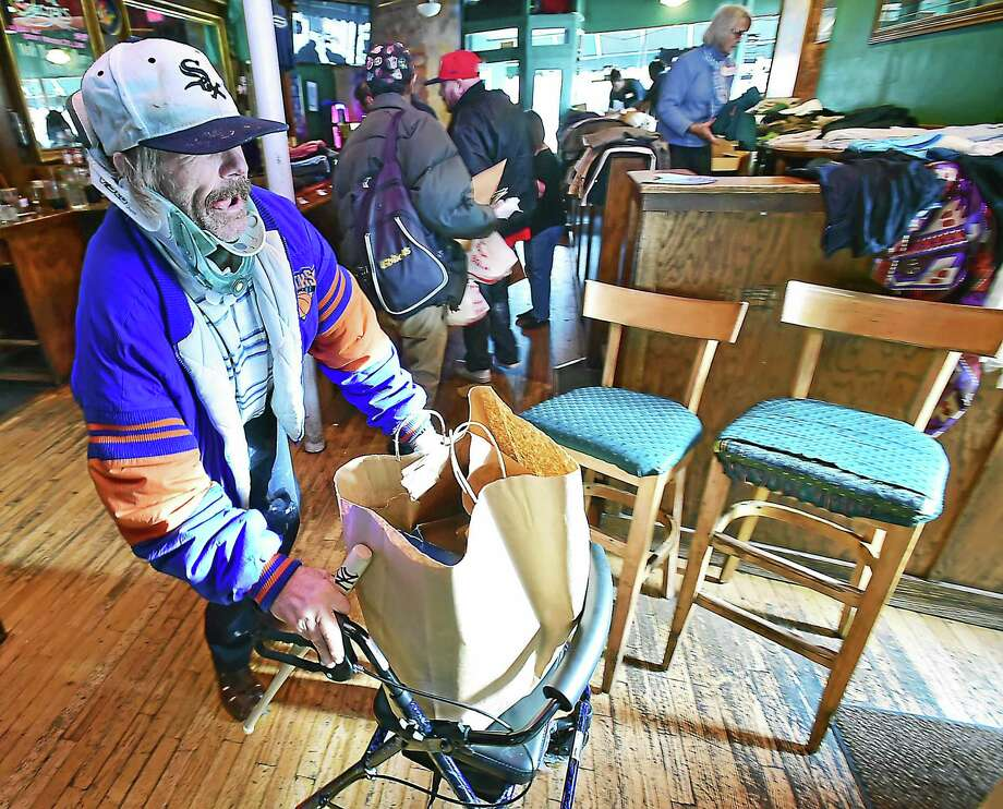 "New Haven resident Randall Schappa leaves Christopher Martins Restaurant on State Street on Thanksgiving day, Novemver 26, 2015, with bags of clothing, canned food and toiletries after enjoying a three-course sitdown turkey dinner run entirely by volunteers. Scappa said, ""superb, everything is superb.""  (Catherine Avalone - New Haven Register) Photo: Journal Register Co. / New Haven RegisterThe Middletown Press"