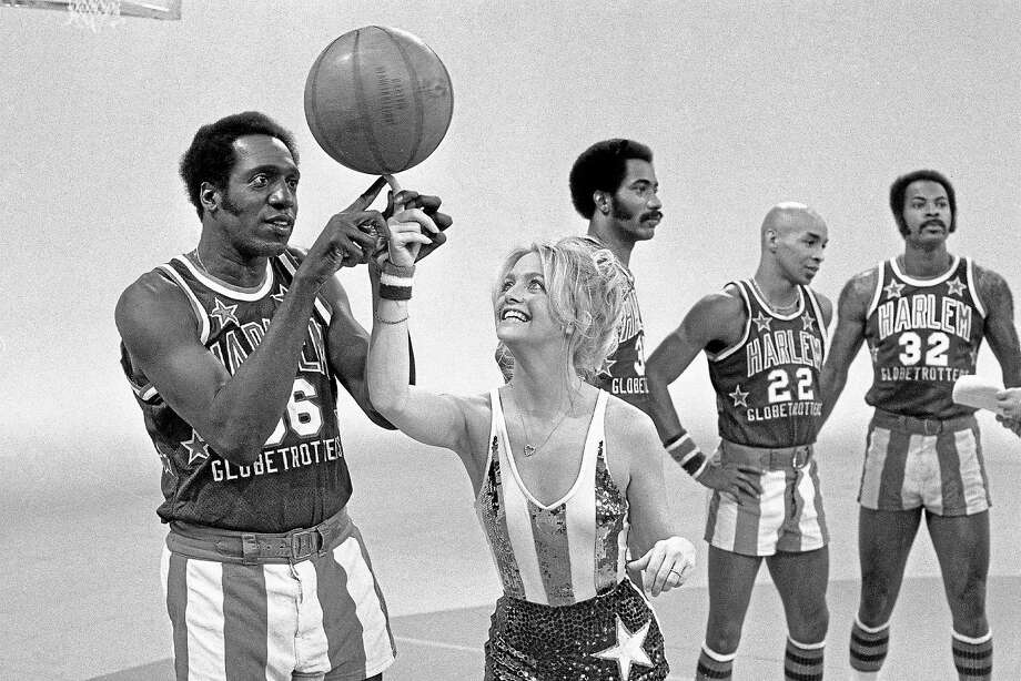 Actress Goldie Hawn has her finger guided to the basketball by Harlem Globetrotters' Meadowlark Lemon, during the taping of her CBS special in Burbank, Calif., Feb. 2, 1978. In the background are teammates Curley Neal and Robert Paige, other player is unidentified. Photo: Associated Press   / 1978 AP