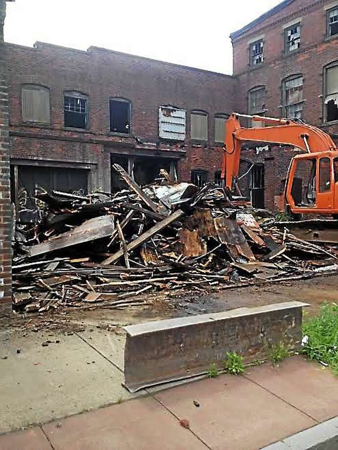 A wooden portion of building at 142 River St. was demolished Friday after small fire. Photo: Mary O'Leary — New Haven Register