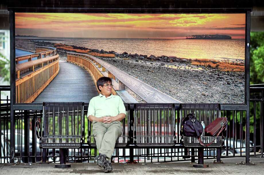 A man waits for a southbound train out of the rain at the Milford train station 9/10/2015. Photo: Arnold Gold — New Haven Register File Photo