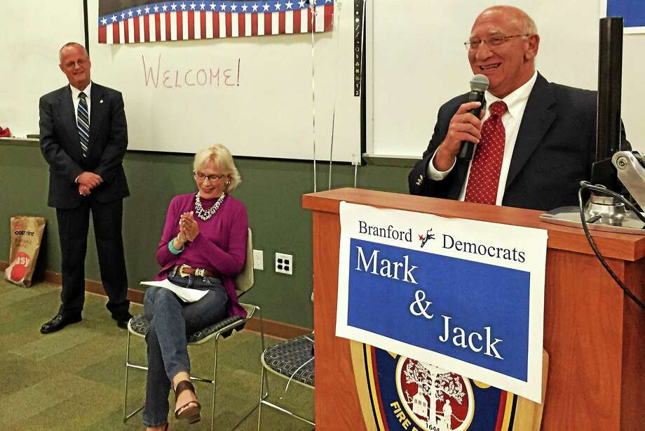 Mark Rabinowitz, right, delivers remarks after earning the Democratic nomination to run for first selectman as state Rep. Lonnie Reed, D-Branford, and Jack Ahern, far left, look on during the party's convention Tuesday. Photo: Esteban L. Hernandez — New Haven Register