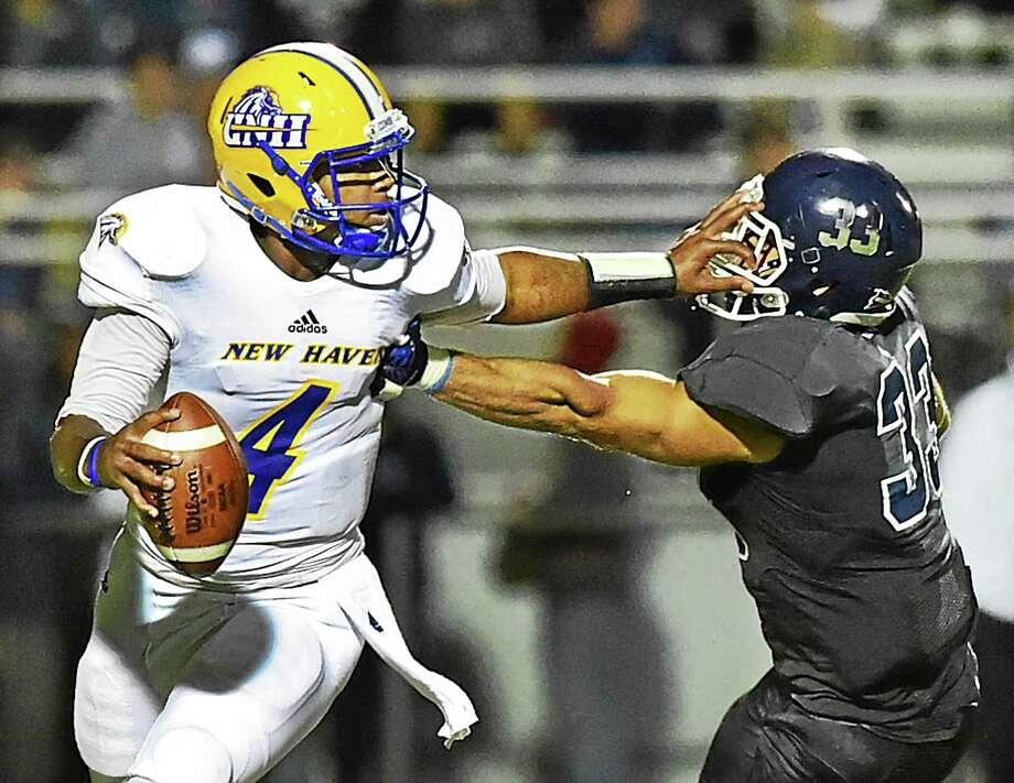 New Haven QB Ajee Patterson stiff-arms SCSU's Vasilios Grigorakos during Friday's game. Photo: Catherine Avalone — Register   / New Haven RegisterThe Middletown Press