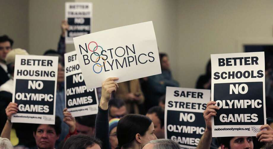 In this Feb. 5 file photo, people hold up placards against the Olympic Games coming to Boston. Photo: Charles Krupa — The Associated Press File Photo   / AP