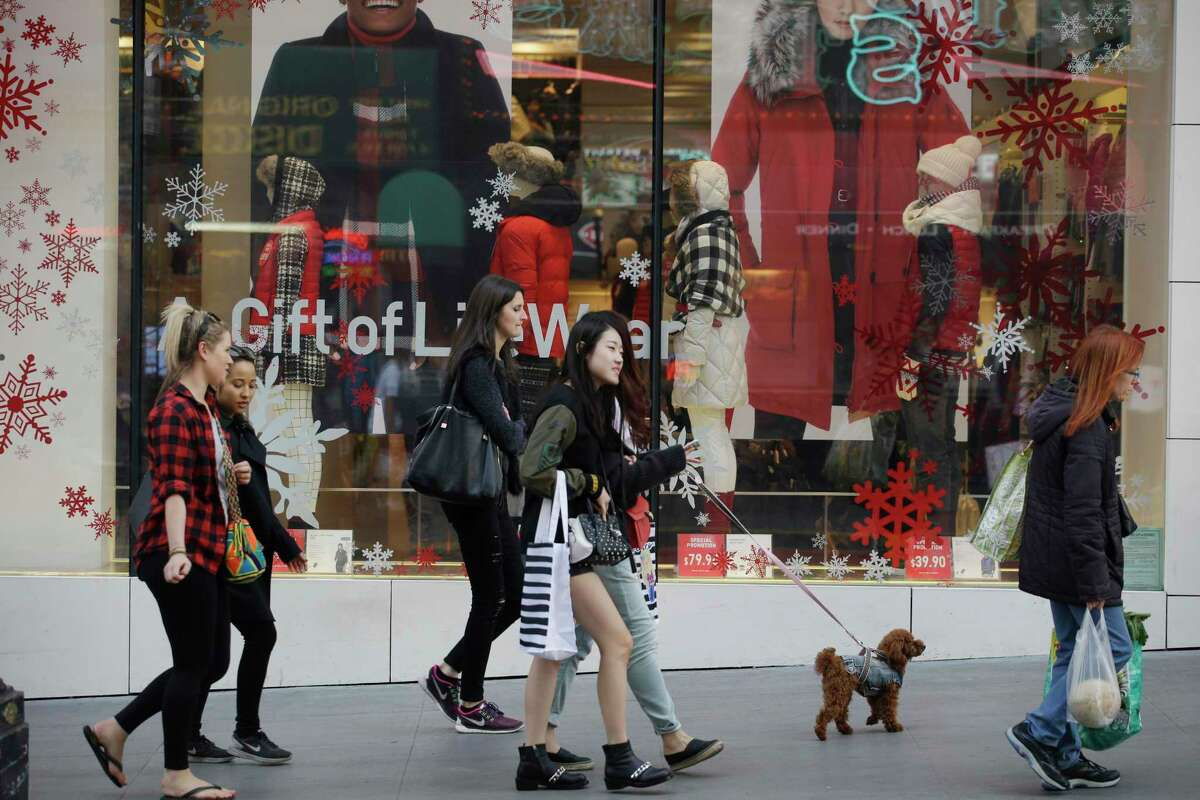In this Sunday, Nov. 22, 2015, file photo, shoppers walk in front of a holiday display in San Francisco. A lack of must-have items, big discounts on winter clothes and pricey toys are defining this year's holiday season.