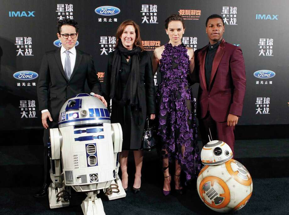 """From left, director J.J. Abrams, producer Kathleen Kennedy, actress Daisy Ridley and actor John Boyega pose with droids character BB-8 and R2-D2 on stage during the premiere of """"Star Wars: The Force Awakens"""" in Shanghai, China, Sunday. Photo: Chinatopix Via Associated Press   / CHINATOPIX"""