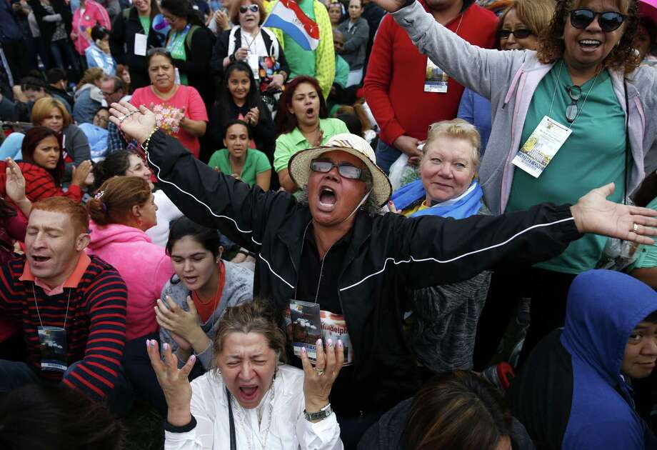 Inocencia Polanco, of Philadelphia and originally form the Dominican Republic, center  in hat, joined by Freddy Espana of Honduras, left in striped shirt, and Maria Zuleta of Columbia, low center in white, pray a novena together as they crowd into Independence Mall ahead of Pope Francis' speech outside Independence Hall in Philadelphia, Saturday, Sept. 26, 2015. Photo: AP Photo/Carolyn Kaster    / AP