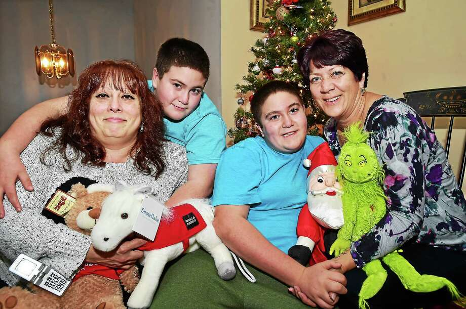 CATHERINE AVALONE — NEW HAVEN REGISTER  Lynn Tommessilli, at left, with long-time family friend Dianna E. Schatzlein-Ahern in her East Haven home with her 11-year-old twins, Stevie, left, and Eddie Ahern. Photo: Journal Register Co. / New Haven RegisterThe Middletown Press
