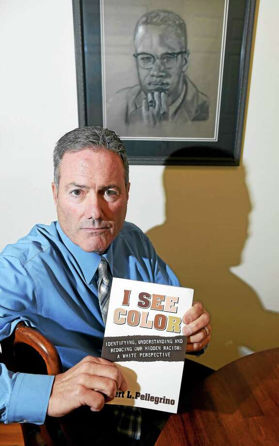 """(Arnold Gold-New Haven Register)  Attorney Robert Pellegrino with his book """"I See Color, Identifying, Understanding and Reducing Our Hidden Racism: A White Perspective,"""" in his office in New Haven. Photo: Journal Register Co."""