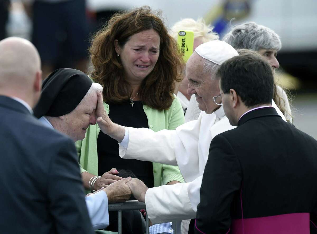 Pope Francis stops to meet people after arriving at Philadelphia International Airport in Philadelphia, Saturday, Sept. 26, 2015. The Pope will spend the last two of his six days in the U.S. in Philadelphia as the star attraction at the World Meeting of Families, a conference for more than 18,000 people from around the world that has been underway as the pope traveled to Washington and New York.