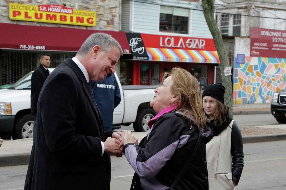 New York Mayor Bill de Blasio, left, talks with Kathleen Morris on Nov. 12, 2015 in the Queens borough of New York. Photo: AP Photo/Mark Lennihan   / AP