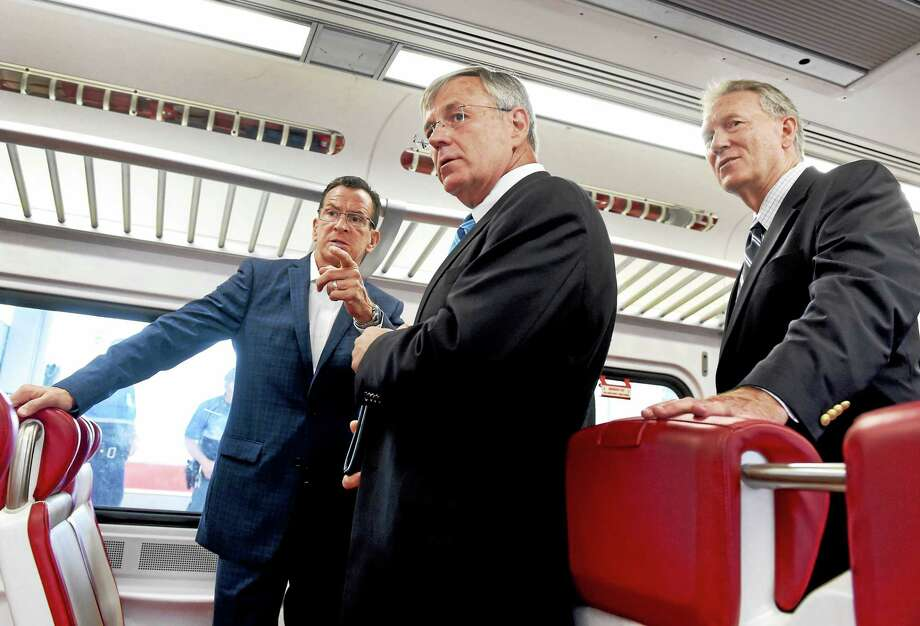 (Peter Hvizdak - New Haven Register)  Connecticut Governor Dannel P. Malloy, left, Connecticut D.O.T. Commissioner James Redeker, center, and John Hartwell, Vice-Chair of the CT Commuter Rail Council, right, tour an M-8 commuter rail car after a press conference at Union Station in New Haven Monday afternoon July 27, 2015 to provide updates regarding major upgrades to the New Haven Line, providing more convenience for riders. Photo: ©2015 Peter Hvizdak / ©2015 Peter Hvizdak