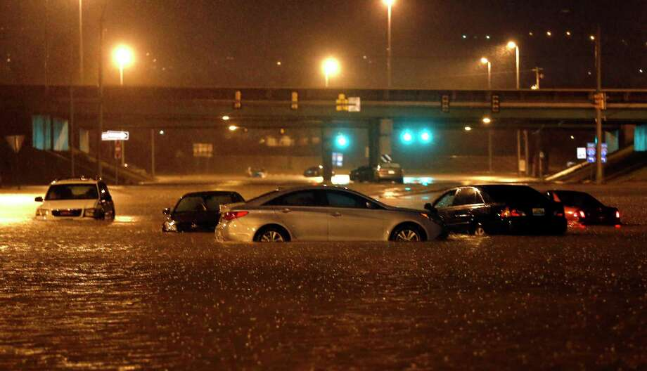 Cars sit submerged in flood waters on Tallapoosa Street, Friday, Dec. 25, 2015, in Birmingham, Ala. A Christmastime wave of severe weather continued Friday as a tornado touched down in north-central Alabama, including part of Birmingham, the state's largest city. Photo: AP Photo/Butch Dill / FR111446 AP