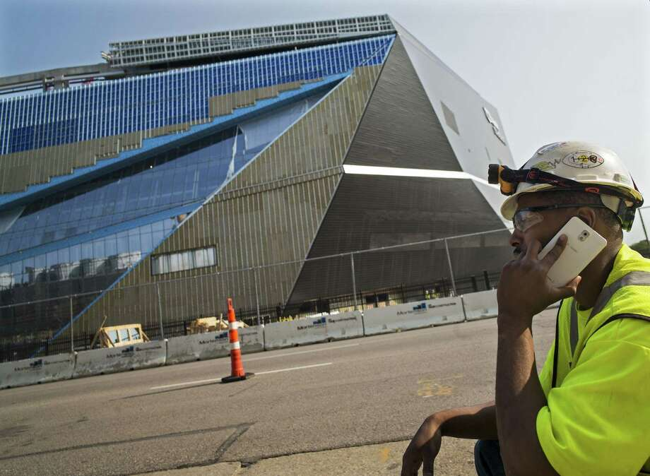 Apprentice electrician Coshay Murray talks on a phone in front of the Minnesota Vikings' new stadium in Minneapolis on Wednesday. Photo: Richard Tsong-Taatarii — Star Tribune   / Star Tribune