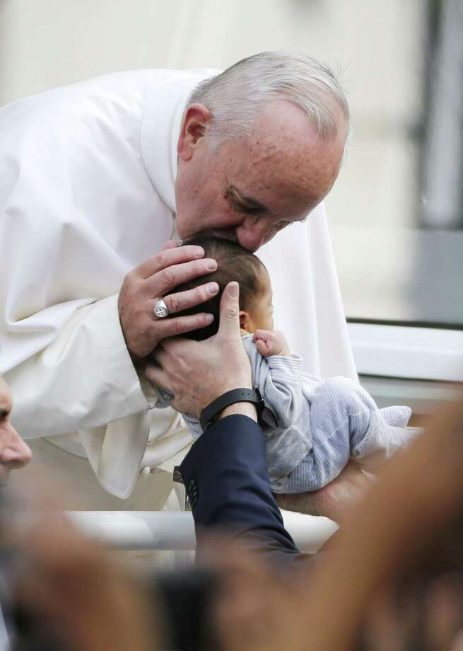 Pope Francis passes the crowd and kisses a baby in his pope mobile in Philadelphia on Saturday, Sept. 26, 2015. The pope spoke at Independence Hall on his first visit to the United States. Photo: (Jim Bourg/Pool Photo Via AP) / Reuters Pool