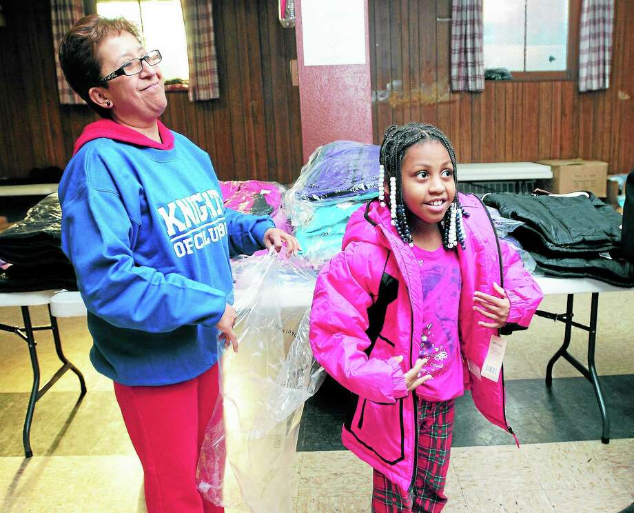 Ana Romero, left, helps Kaylee Adams, 5, of New Haven find the right size during the Knights of Columbus Coats for Kids distribution at St. Rose of Lima Church in the Fair Haven section of New Haven in 2013. Photo: Arnold Gold — New Haven Register