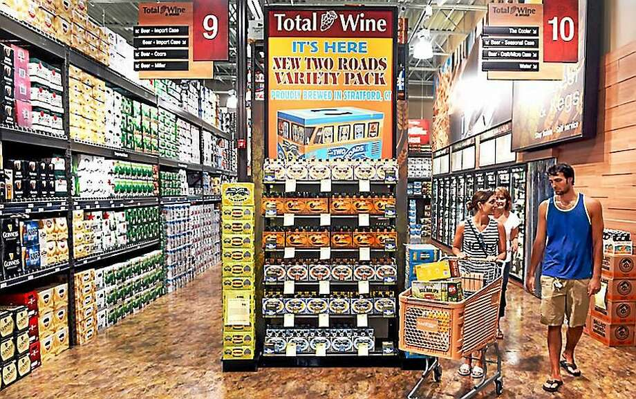 Left to right, Christine Noi, her mother, Darlene Coppola, and husband, Daniel Noi, shop in the beer section at Total Wine & More at 230 Cherry St. in Milford. Photo: Photo By Arnold Gold -- New Haven Register
