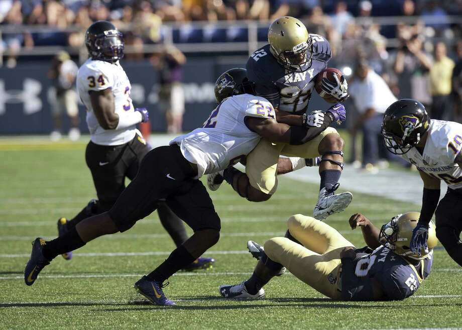 Navy slotback Toneo Gulley is stopped by East Carolina's Terrell Richardson during a game earlier this season. Photo: The Associated Press File Photo   / Capital Gazette