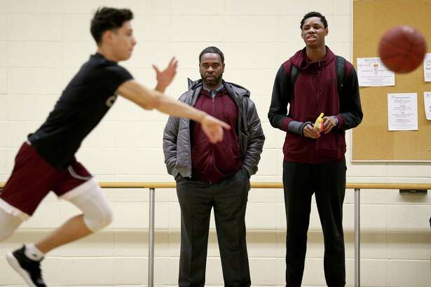 St. Anthony assistant coach Hennssy Auriantal (center left) talks with star player Charles Bassey before the game with Virginia Episcopal School at the Nassau Community College gym in Garden City, N.Y.