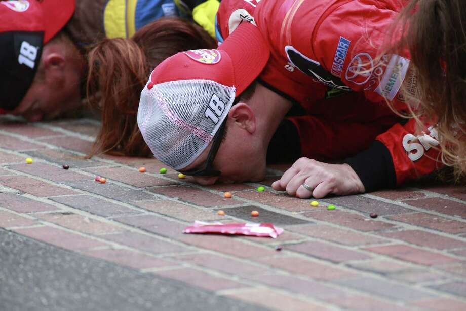 Sprint Cup Series driver Kyle Busch kisses the bricks on the start/finish line after winning the Brickyard 400 at Indianapolis Motor Speedway on Sunday. Photo: R Brent Smith — The Associated Press   / FR171017 AP