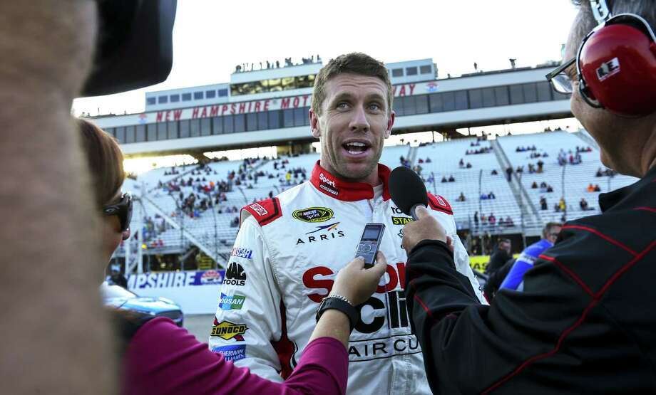Carl Edwards gives interviews after winning the pole for Sunday's NASCAR Sprint Cup series race at New Hampshire Motor Speedway. Photo: Cheryl Senter — The Associated Press   / FR62846 AP