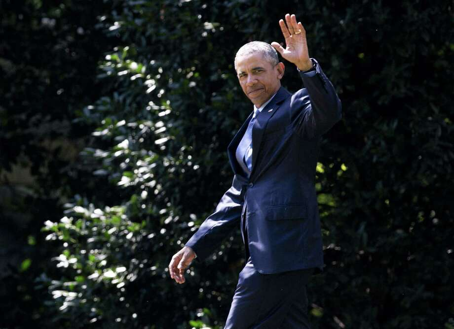 President Barack Obama waves as he walks from the Oval Office of the White House in Washington Monday to board Marine One for a short trip to Andrews Air Force Base, Md., before traveling to Las Vegas, Nev., to speak at the National Clean Energy Summit. Photo: AP Photo   / AP