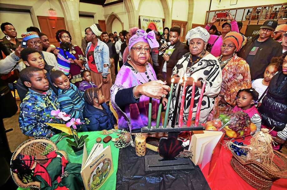 """Families gather around Gloria Richardson during the candle lighting ceremony at """"Rekindling Kwanzaa Principles"""" presented by the Community Kwanzaa Association of New Haven, Saturday, Dec. 26, 2015, at the Afro-American Cultural Center on Park Street in New Haven. To Richardson's left is Malcolm Welfare who read the meaning of each candle, Constance Thomas-Razza and event chair Elaine Richardson. The theme for this year, """"Having Courage in the Face of Adversity."""" Photo: Catherine Avalone — New Haven Register    / New Haven RegisterThe Middletown Press"""