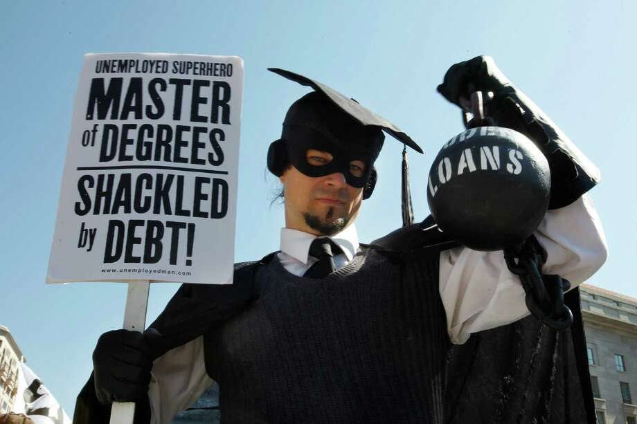 "In this Oct. 6, 2011, photo, Gan Golan, of Los Angeles, dressed as the ""Master of Degrees,"" holds a ball and chain representing his college loan debt, during Occupy DC activities in Washington. Photo: AP File Photo   / AP"