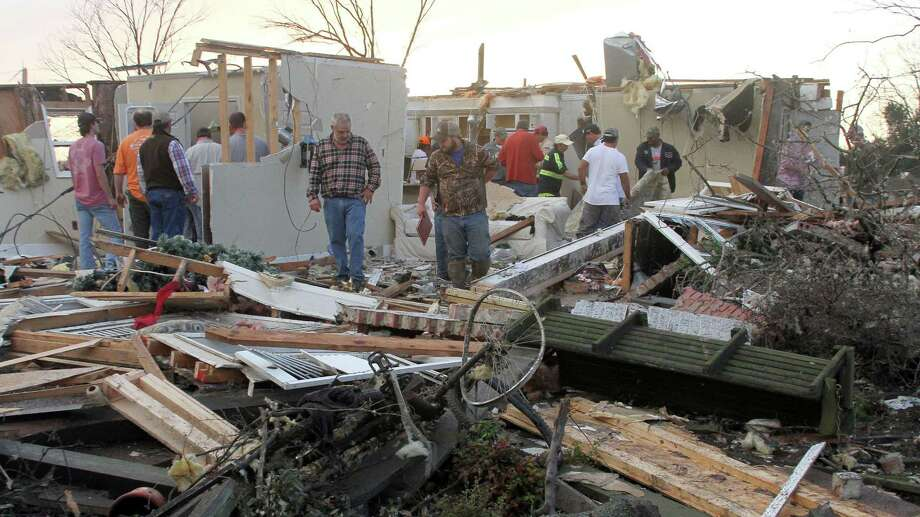"""People inspect a storm-damaged home in the Roundaway community near Clarksdale, Miss. on Dec. 23, 2015. A storm system forecasters called """"particularly dangerous"""" killed multiple people as it swept across the country Wednesday. Photo: Troy Catchings/The Press Register Via AP   / The Press Register"""