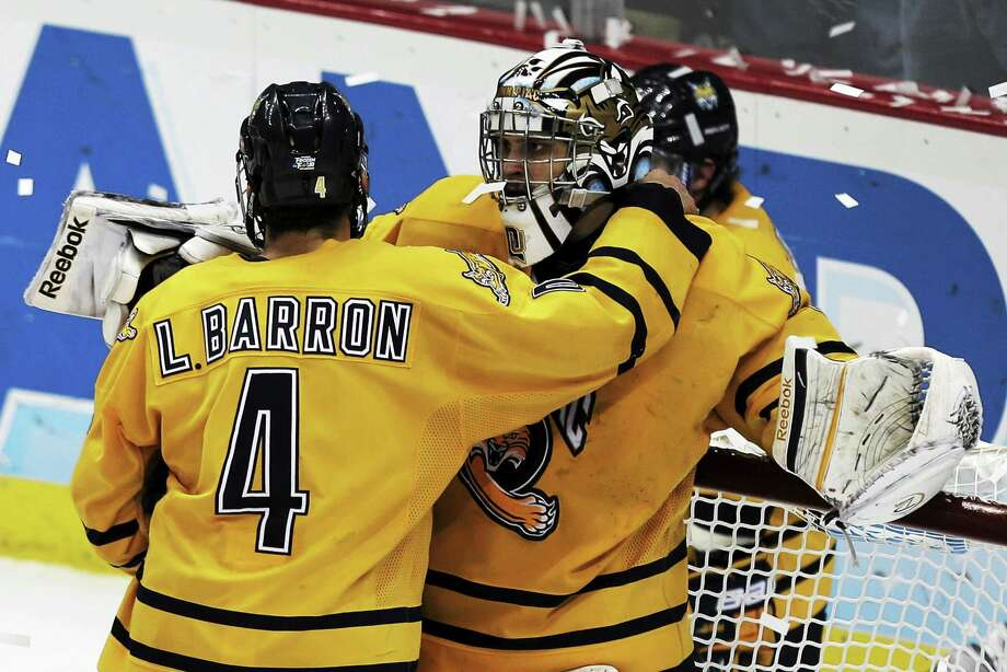 The Quinnipiac goalie Eric Hartzell, right, is comforted by Loren Barron (4) after losing to Yale 4-0 in the NCAA men's college hockey national championship game in Pittsburgh Saturday, April 13, 2013. Photo: AP / AP2013